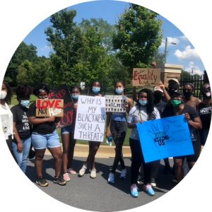 "black activists holding signs reading ""Love not hate"", ""Why is my blackness such a thread?"", ""BLM"", ""Equality"", ""Stop killing us"""