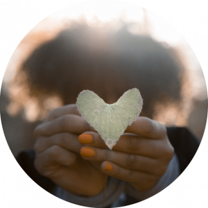 heart-shaped leaf held by black woman hands